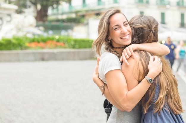 屋外で彼女の友人を抱擁している幸せな女性 無料写真