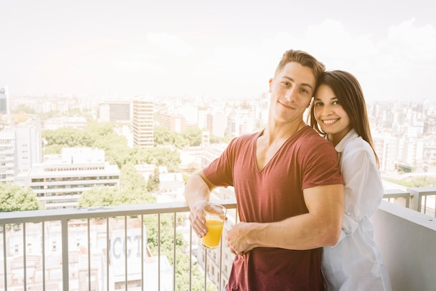 Happy woman hugging man with juice glass on balcony Free Photo