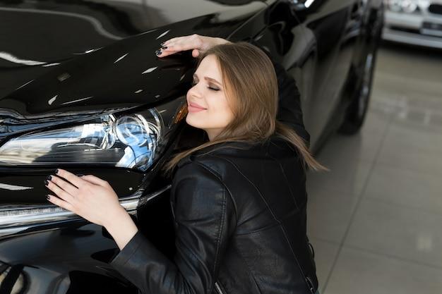 Счастливая женщина обнимает капот своей новой машины Premium Фотографии