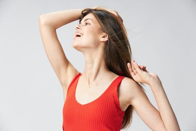 赤いtシャツを着た幸せな女が彼女の手で彼女の頭の髪に触れて側に見える Premium写真