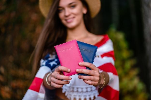アメリカの国旗と彼女の手でパスポートと麦わら帽子で幸せな女 Premium写真
