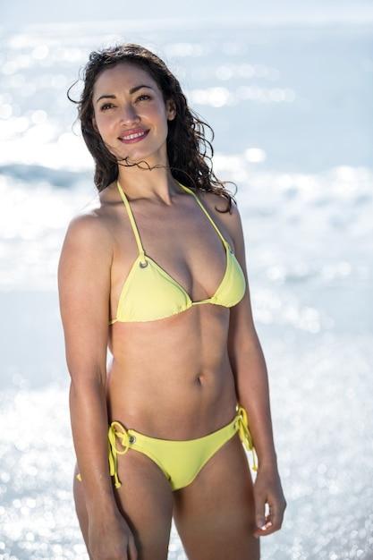 Счастливая женщина в бикини, стоя на берегу моря Premium Фотографии