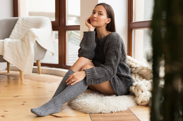 敷物の上に座って居心地の良い服を着た幸せな女性 無料写真