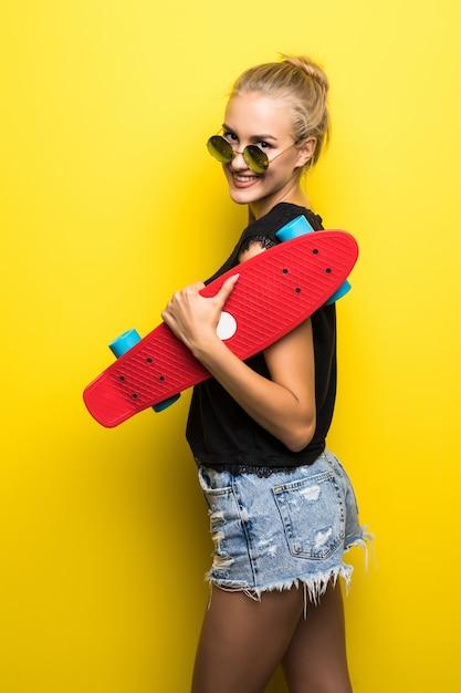 Счастливая женщина в джинсовой одежде и солнцезащитных очках со скейтбордом веселится и смотрит в камеру на желтом фоне Бесплатные Фотографии