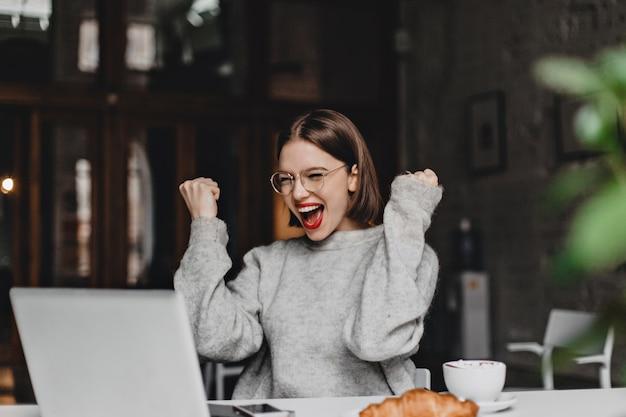 眼鏡をかけた幸せな女性は勝利のジェスチャーをし、心から喜んでいます。ノートパソコンを見て灰色のセーターを着た赤い口紅の女性。 無料写真