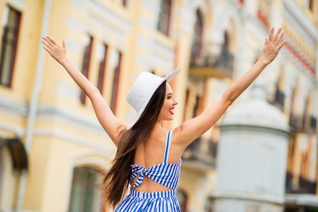 밀 짚 모자와 함께 포즈를 취하는 여름 드레스에 행복 한 여자 프리미엄 사진