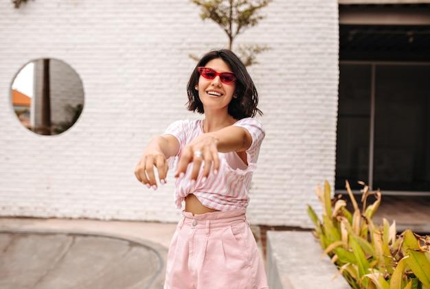 手を伸ばして通りでポーズをとるサングラスの幸せな女性。ピンクのtシャツで日焼けした女性の屋外ショット。 無料写真