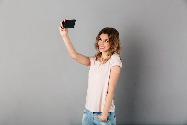 회색에 주머니에 팔을 잡고 스마트 폰에 티셔츠를 만드는 셀카에서 행복한 여자 프리미엄 사진