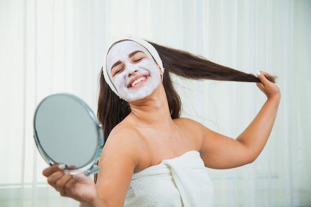 수건과 얼굴 마스크에 행복 한 여자는 거울을 봐. 홈 뷰티 트리트먼트. 스킨 케어 및 회춘 개념. 프리미엄 사진