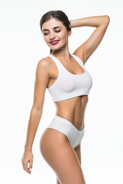 Счастливая женщина в белом нижнем белье подходит на белой стене Бесплатные Фотографии