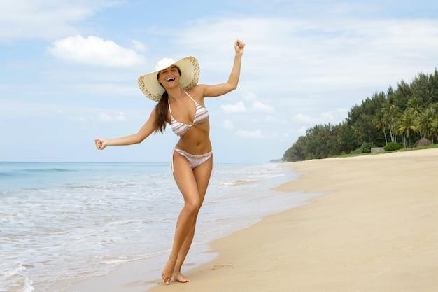 Happy woman is walking on the sea coast Premium Photo