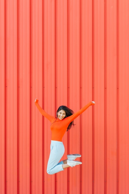 Happy woman jumping against red corrugated background while arm outstretched Free Photo
