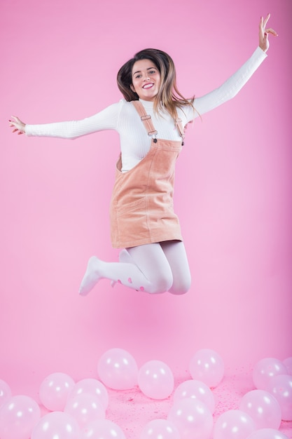 Happy woman jumping on floor with air balloons Free Photo