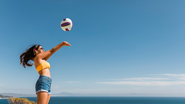 Happy woman jumping and throwing ball Free Photo