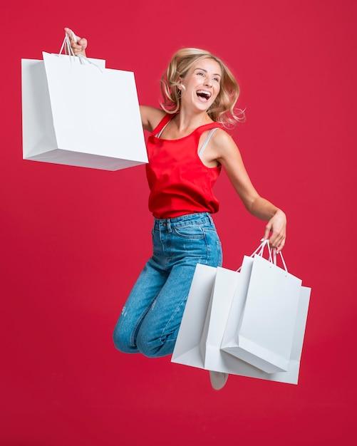 Donna felice che salta con molte borse della spesa Foto Gratuite