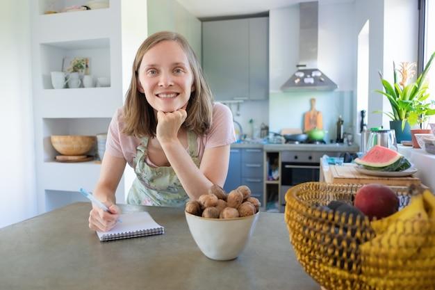 果物とナッツのキッチンでカウンターに寄りかかって、ノートにメモを書いてカメラ目線の幸せな女。家庭料理のコンセプト 無料写真
