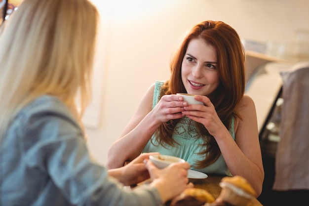 Happy woman listening to friend at coffee shop Premium Photo