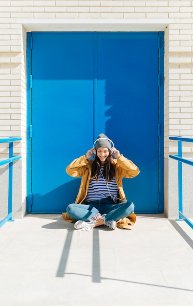 Happy woman listening music on smart phone sitting  against blue door outdoors Free Photo