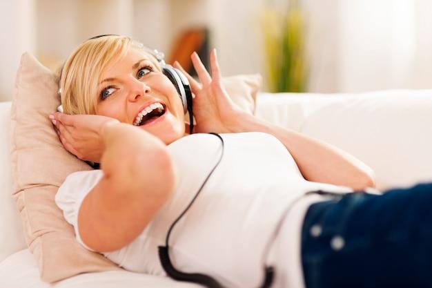 Donna felice che ascolta la musica sul divano Foto Gratuite