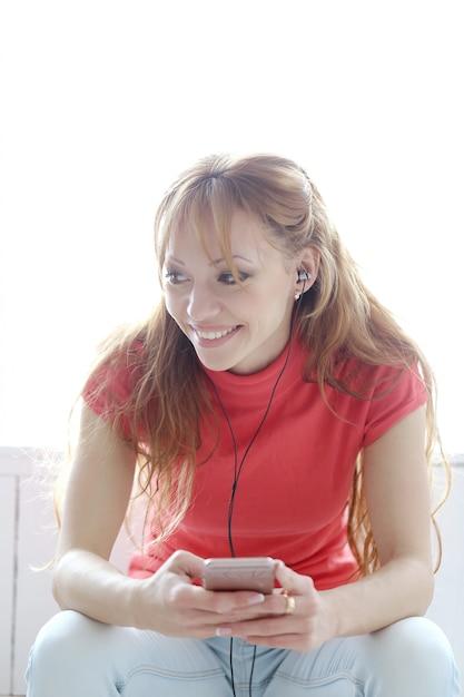 Musica d'ascolto della donna felice con le cuffie Foto Gratuite