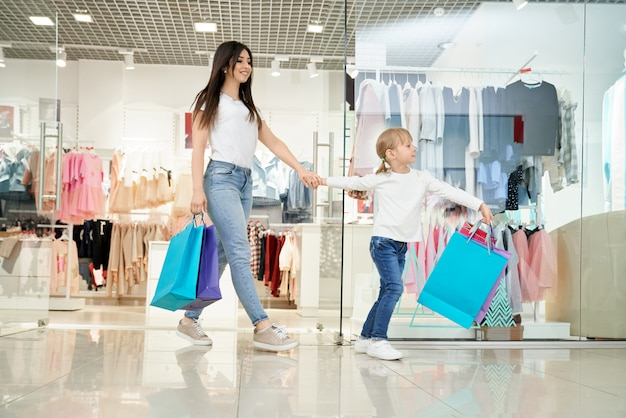 Happy woman and little daughter going out from store in mall Free Photo