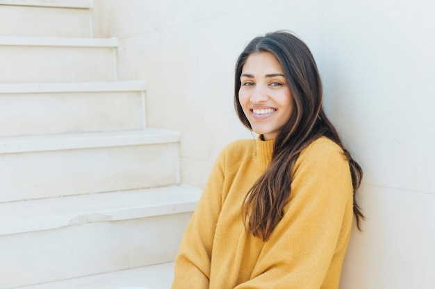Happy woman looking at camera sitting on staircase Free Photo