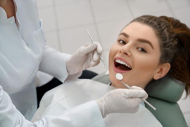 Happy woman lying in dentist chair, posing. Premium Photo
