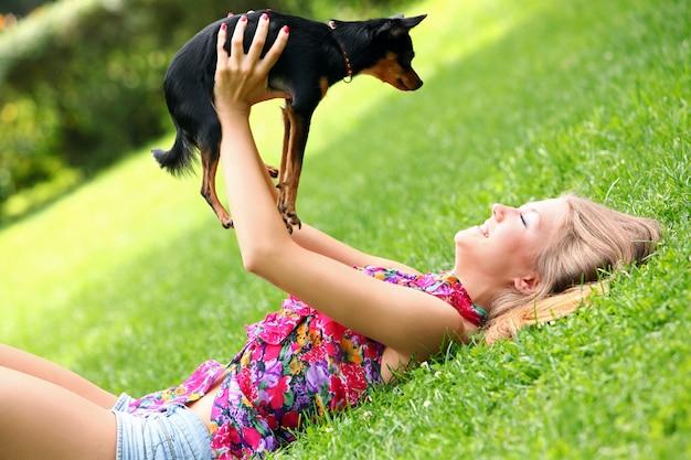 彼女の犬と草の上に横たわる幸せな女 無料写真