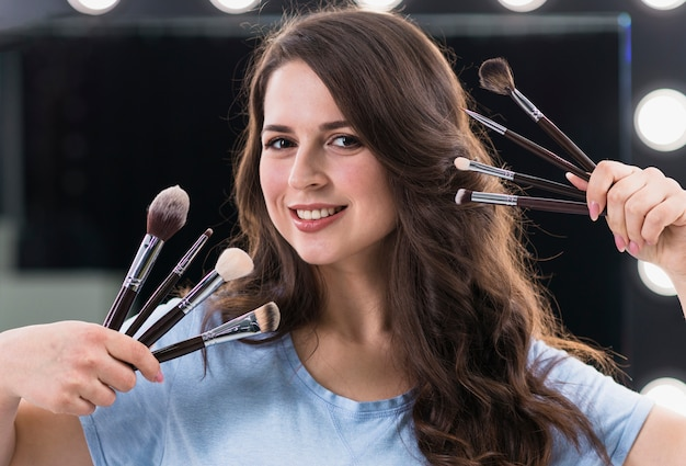 Happy woman makeup artist with brushes Free Photo