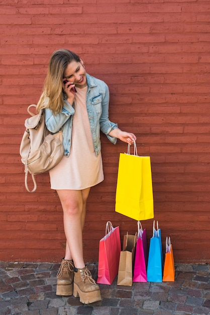 Happy woman near bright shopping bags talking by phone Free Photo