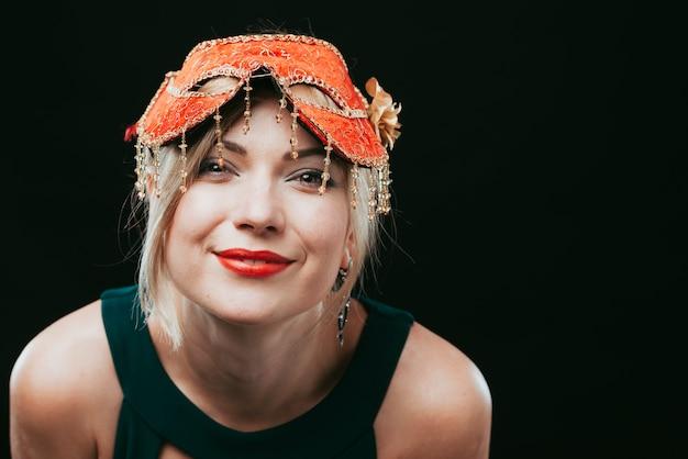 Happy woman in orange carnival mask Free Photo