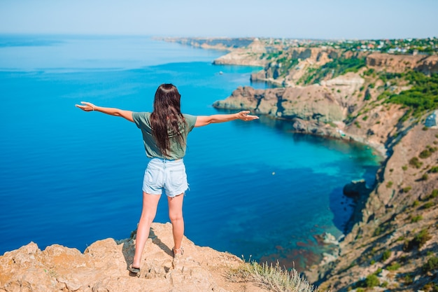 Счастливая женщина на открытом воздухе на краю обрыва наслаждается видом на скалу на вершине горы Premium Фотографии