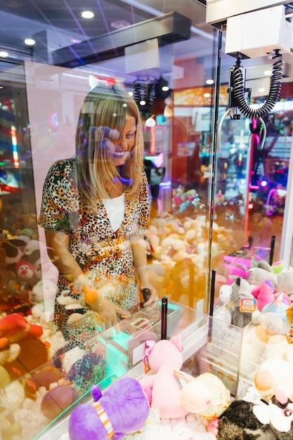 Happy woman playing arcade machine Free Photo