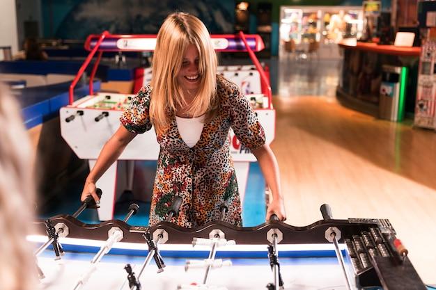 Happy woman playing foosball Free Photo