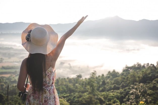Happy woman pointing on the viewpoint Free Photo