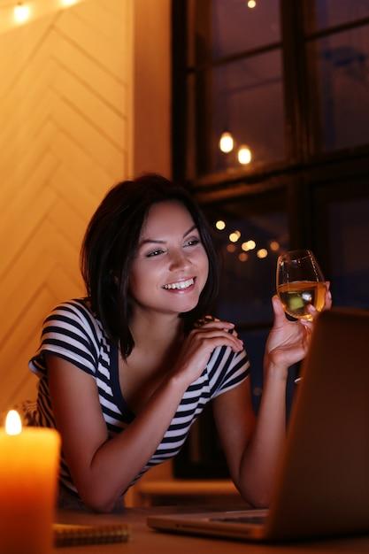 Pc画面を見てワインのグラスと幸せな女の肖像画 無料写真