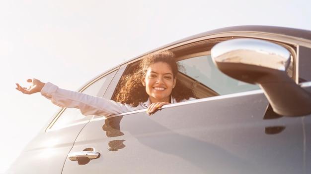 Счастливая женщина позирует из окна Бесплатные Фотографии