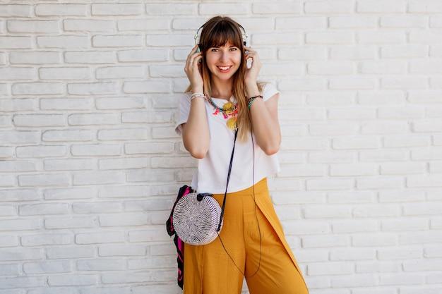 Счастливая женщина позирует над белой кирпичной стеной с наушниками. Бесплатные Фотографии
