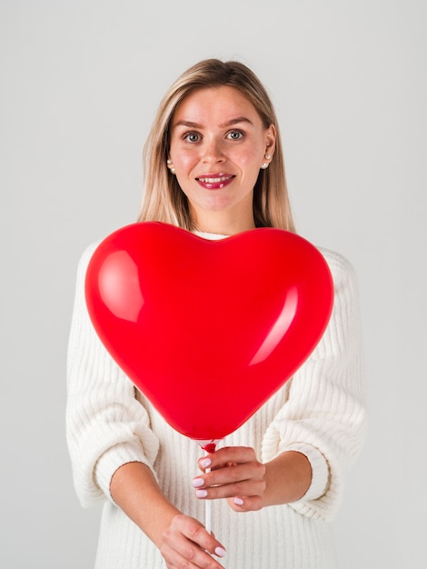 Happy woman posing with balloon for valentines Free Photo