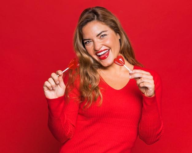 막대 사탕과 함께 포즈를 취하는 행복 한 여자 무료 사진