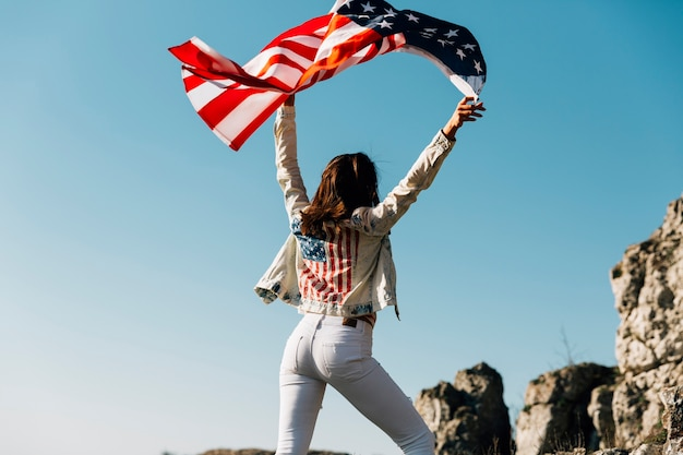 Happy woman raising hands with american flag Free Photo
