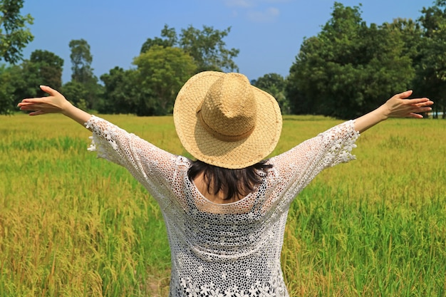 Happy woman raising her arms in the paddy field full of ripe rice plants ready for harvesting Premium Photo