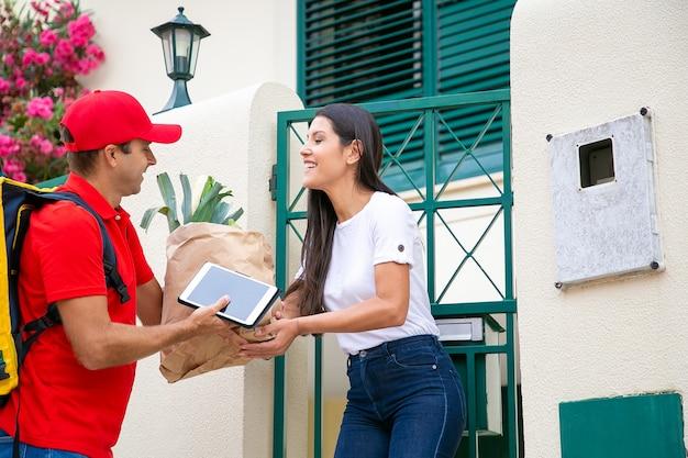 식료품 점에서 음식을받는 행복 한 여자, 그녀의 문에서 택배에서 패키지를 복용. 배송 또는 배달 서비스 개념 무료 사진
