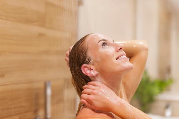 Donna felice che si distende sotto la doccia Foto Gratuite