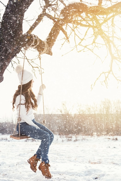 Happy woman and rope swing in winter landscape Premium Photo