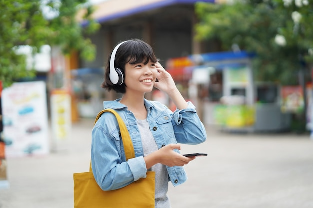 Happy woman shopping with listening to music on smartphone and holding tote bag Premium Photo