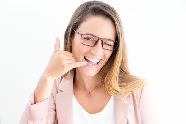 Happy woman showing call gesture and winking Free Photo