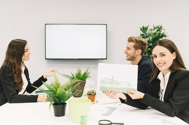 Happy woman showing energy saving concept on paper in office Free Photo