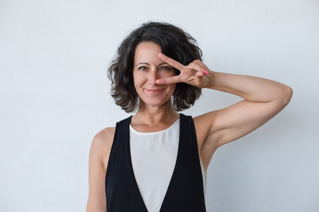 Happy woman showing peace sign Free Photo