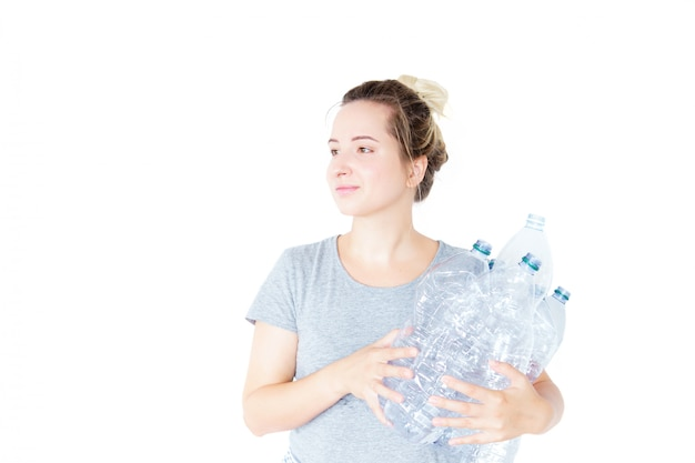 Happy woman shows and holding recyclable plastic bottle isolated. blurry effect. recycling concept. waste separate collection. Premium Photo